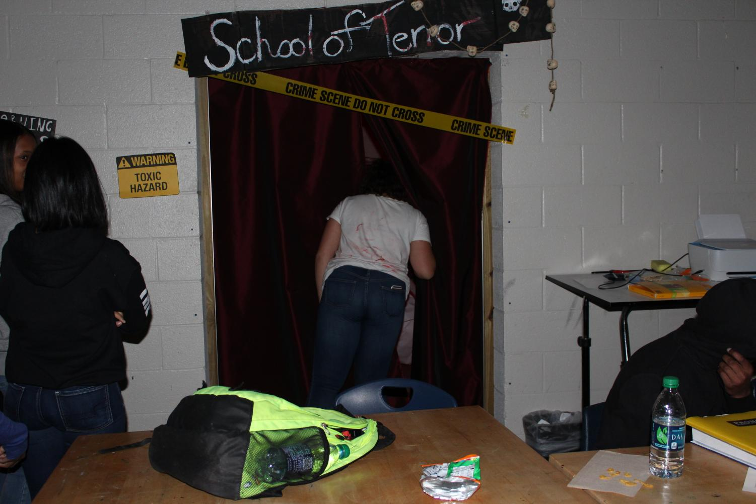 """NC students in art club created a haunted house in Mrs. Dowling's Room for Halloween. """"It took us about a good week to do it. Students used it as an extension of their regular activities in the art room; they brought in the necessary supplies and did face painting and all different types of makeup in addition to decorating in there,"""" Mrs. Dowling said. Curious students who congregated outside of the haunted house,  titled """"School of Terror,"""" were advised to keep their eyes open and go all the way through, no matter what."""