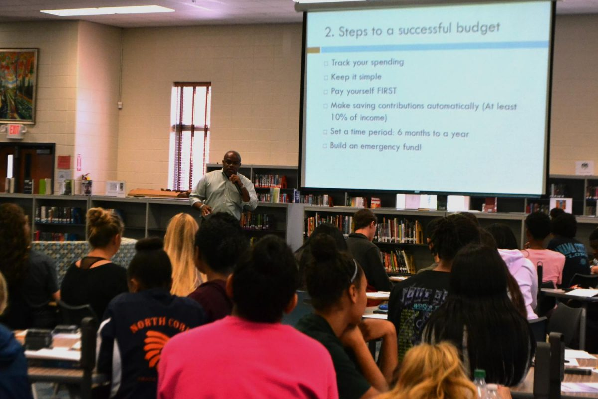 NC's macroeconomics and economics classes gathered in the media center with Dr. Roach and Mr. Marenda to listen to Cliff Robinson discuss budgeting. Robinson involved students in his presentation by interacting with them and asking them questions.