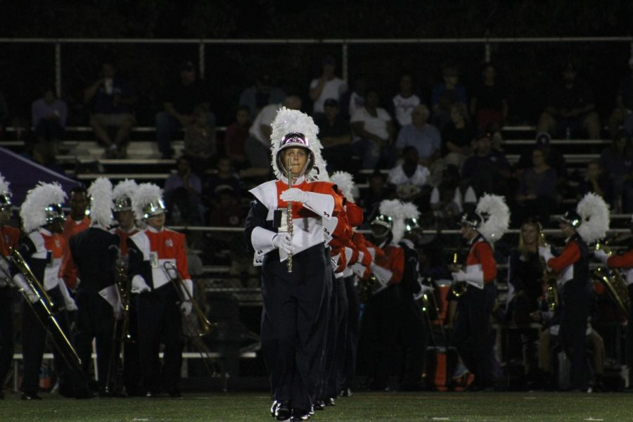NC+band+members+marches+onto+the+field+to+perform+%22Embellish%22+for+the+crowd.+Their+bell-heavy+piece+features+props%2C+costumes%2C+and+aerial+stunts+by+the+colorguard.+