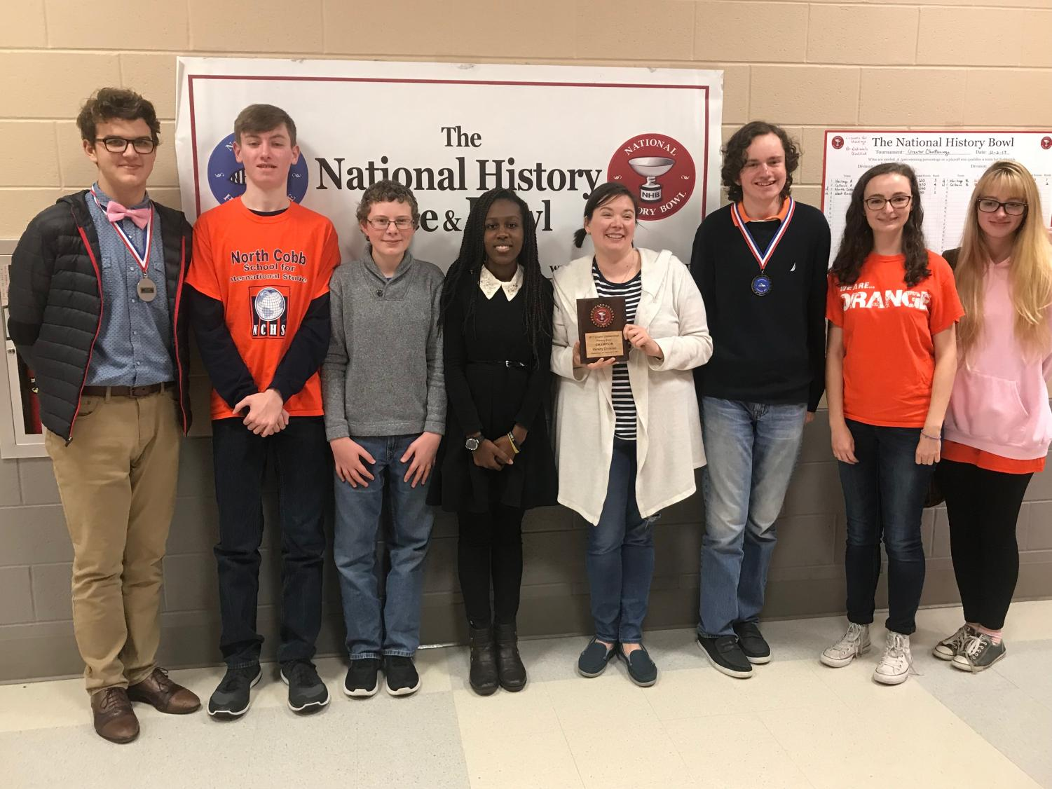 Photo courtesy of Carolyn Glaze. The team of seven joined by NC's chemistry teacher Ms. Tidrick proudly celebrate their victory in The National History Bee and Bowl. Junior Harrison Glaze and sophomore Chandler Quaile stand proudly displaying their medals and flaunting their triumph. The team awaits the the national tournament in Washington D.C.