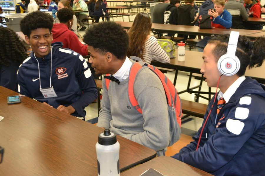 "Tonight the Warriors basketball team will face off against the North Paulding Wolfpack tonight at home; the girls' game begins at 6 PM, and the boys play afterwards at 7:30 PM. Senior varsity players Keanu White, Steven Hubert, and Ginji Ozawa excitedly chattering about their upcoming game at the lunch table. Hubert, pictured in the middle, said, ""Be there or hear about it."""