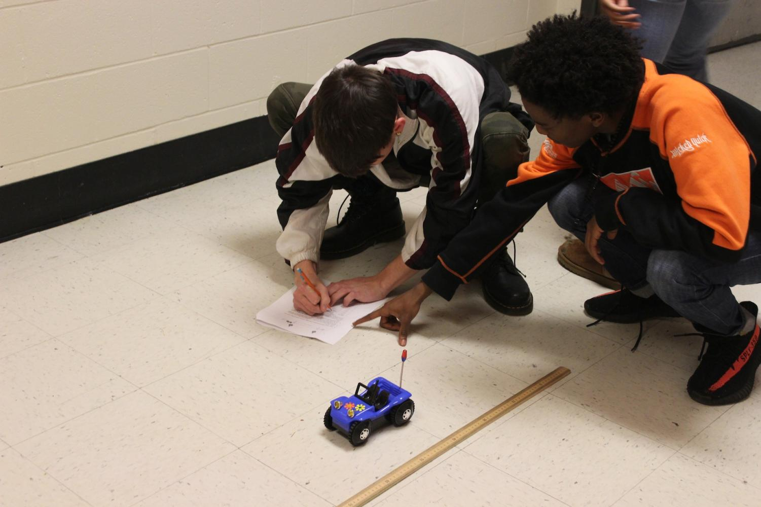 Mrs. Brenna's third period class learns to graph the location of objects with constant velocity cars. The students paired into groups with rulers and toy cars to practice in the hallway.