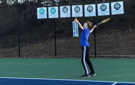 NC tennis player practices his serve and makes the first hit to begin the point and prepare for the tennis season.