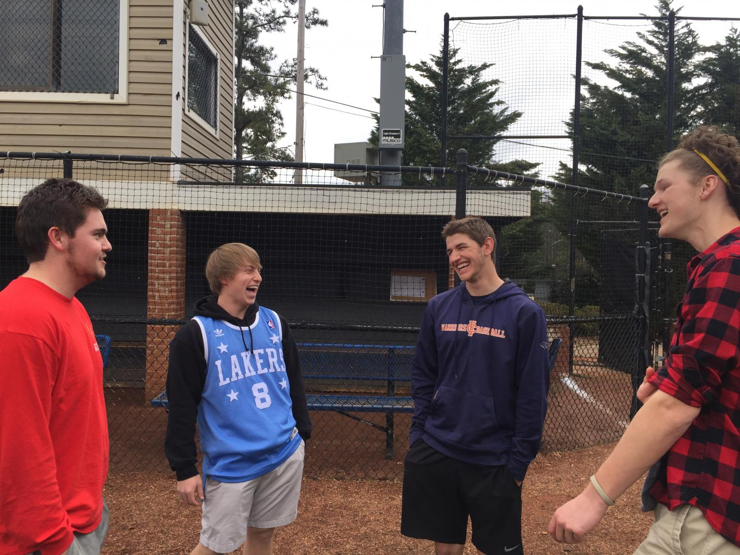 """Christian Tetrault, Zack Lewis, Matthew Terrill, and Gavin Rose (pictured left to right) enjoy some laughs before suiting up for their daily practice. """"Christian always makes sure everyone has a smile on their face,"""" Rose said."""