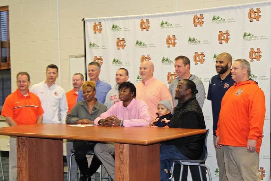 Marking a defining moment, signing day signifies the end of the long grind for the players who have worked hard for their chance to take it to the next level. Pictured above, senior football offensive lineman Curtis Ryans, finalizes his decision among his parents and coaches.