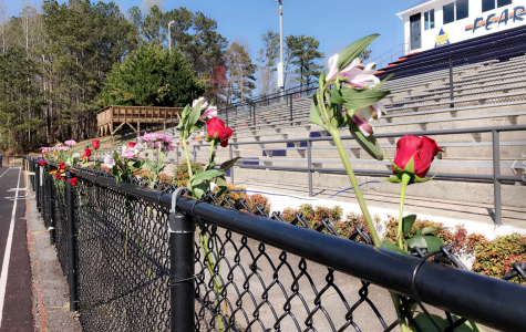 "Students brought flowers to line the fence on the field where the memorial took place. The brainchild of administration and select leaders from each grade, the ceremony aimed to commemorate the teens and adults who fell victim to the Valentine's Day massacre at Douglas County High School. ""Imagine if we came together like this all the time. We wouldn't be having these conversations about gun reform and school shootings if we were constantly supporting each other,"" senior Kaylin Altman said."