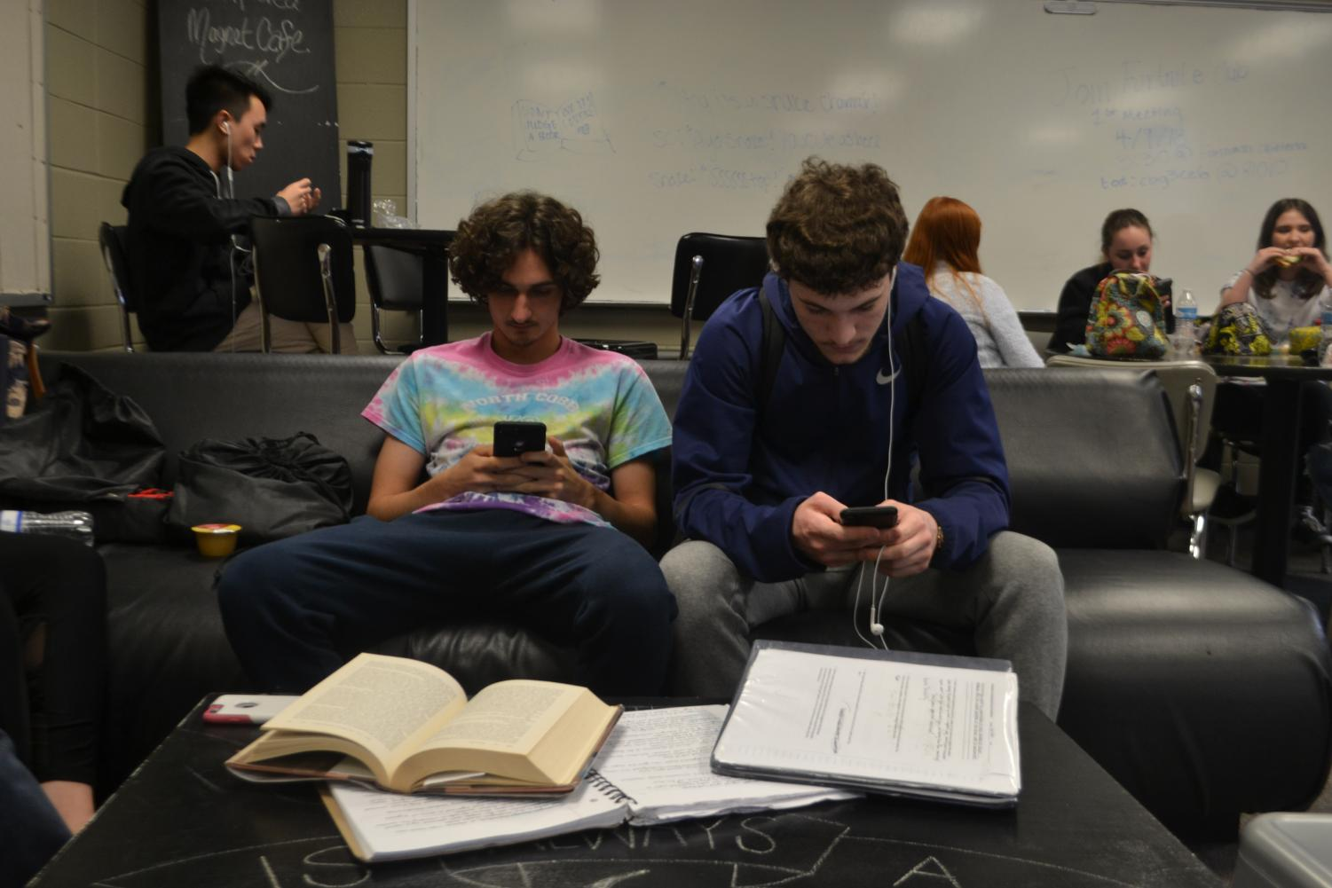 "Magnet seniors Cameron Buxton and Marco Mancuso ignore their homework and busy themselves with looking at their phones. ""Teachers are understanding that it's senior year and kids are starting to unwind and do less school work,"" Mancuso said."
