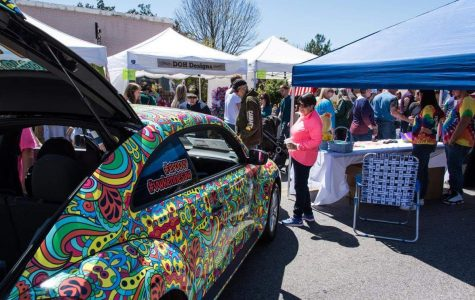 Onlookers mingle among tents showcasing various pieces of art as they take in a vibrant and colorfully painted car.