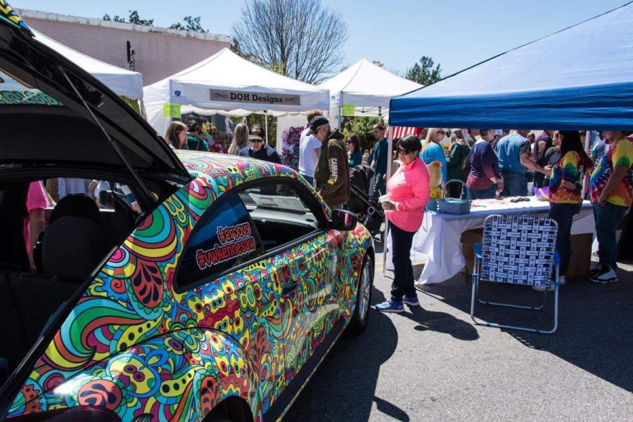 Onlookers+mingle+among+tents+showcasing+various+pieces+of+art+as+they+take+in+a+vibrant+and+colorfully+painted+car.+