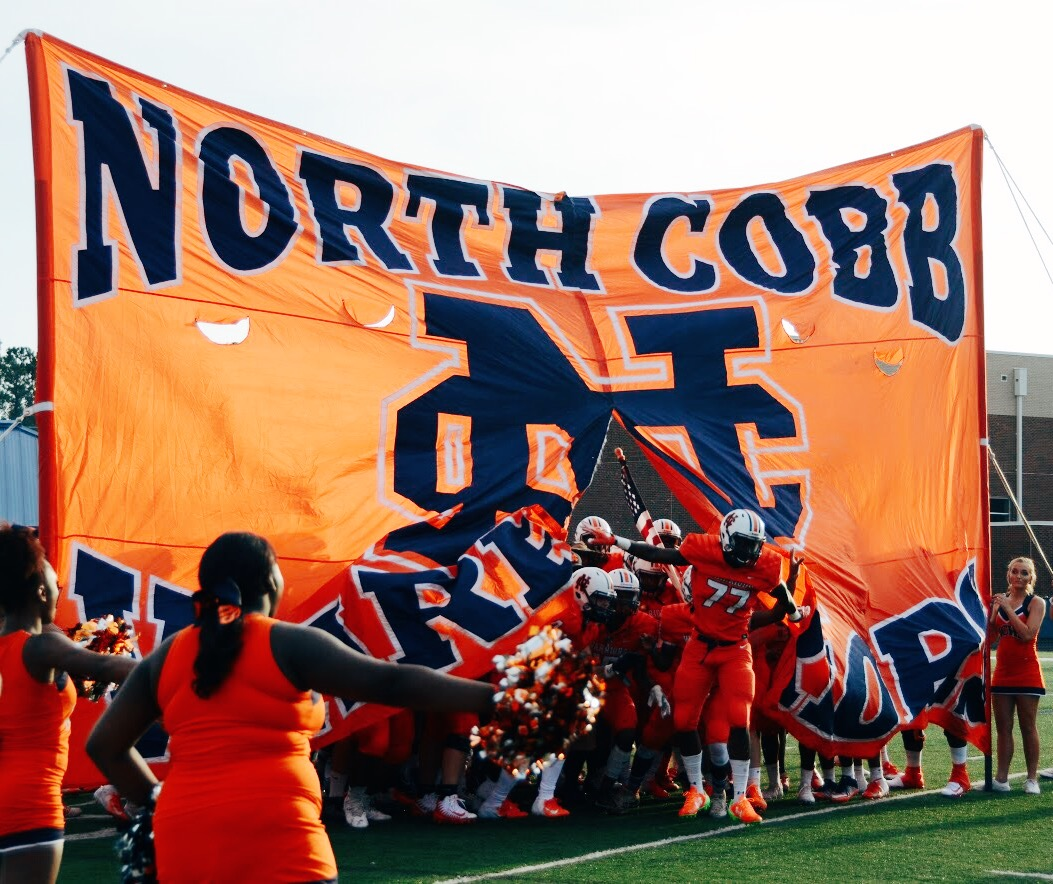 NC's Varsity Football team broke through the flag at the start of the scrimmage, igniting screams and cheers from the crowd of students, parents, and alumni. The team played hard against the Harrison Hoyas on Friday, August 10.