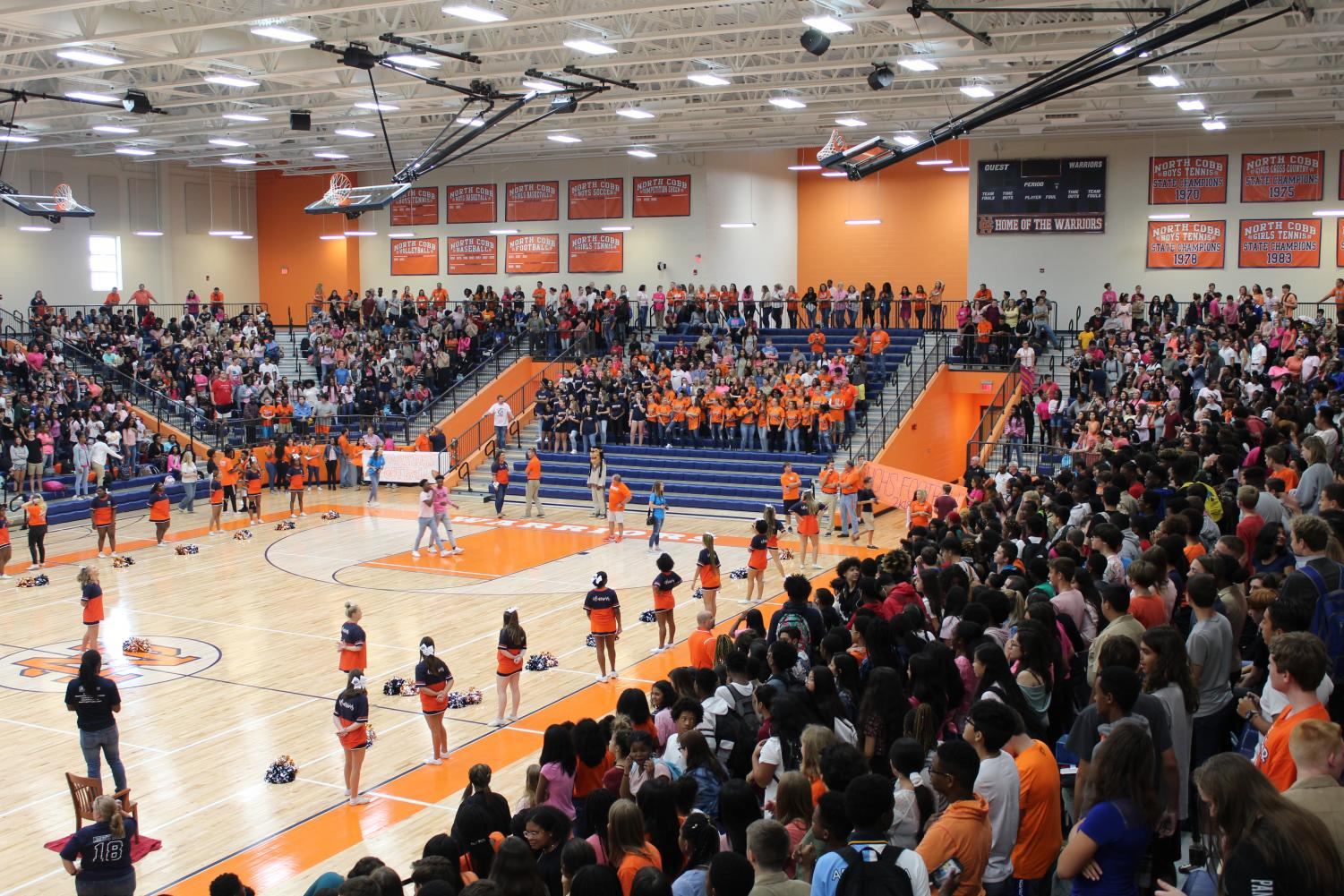 The crowd of more than 2,500 students watch in anticipation as the speakers try to fire up the crowd, leading into the prominent entrance of the football team. The cheerleaders pause their dancing to place a central focus on the team's entrance, serving as a solid start and promotion to the year's football season. The Arena lights eventually dimmed, and a variety of students across the space lit up their cell-phone LED lights, waving them in the air in support of the football players about to race through a  large banner.