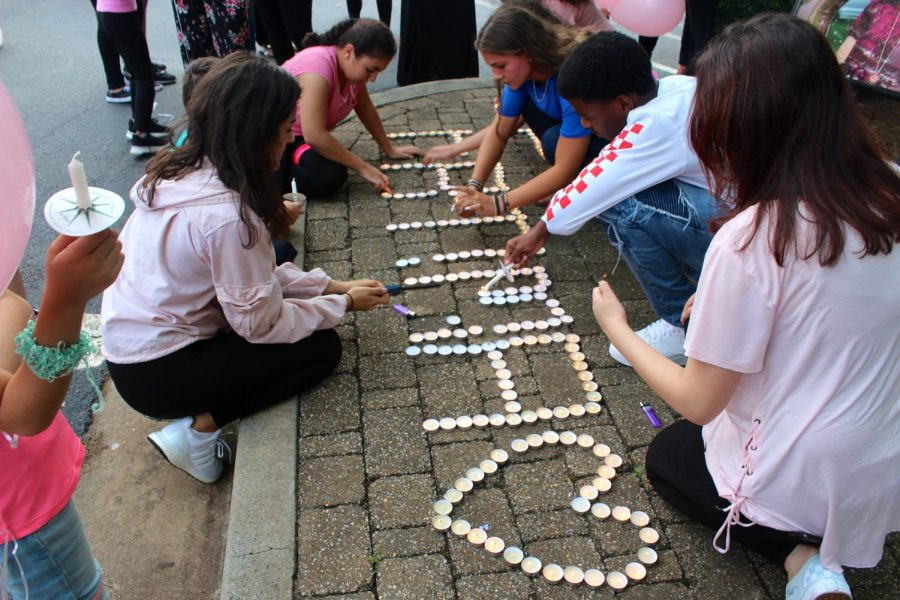 Close friends and family hosted a memorial in honor of junior Fatima Asad's battle against cancer on Wednesday, August 22. Depicted in the picture, students light candles in Asad's name to remember and  set up for the memorial.