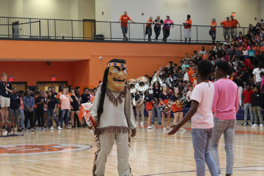 The Warrior mascot, seen with the Spirit Stick, works with pep-rally speakers and seniors Zion Fitch and Chike Asuzu to encourage students to compete for it. With each class growing louder and more energetic, the seniors take charge and win the prize. This was the first time all NC students joined together to participate in the annual Spirit Stick competition, as previously it would be the underclassmen against each other, and the upperclassmen against each other.