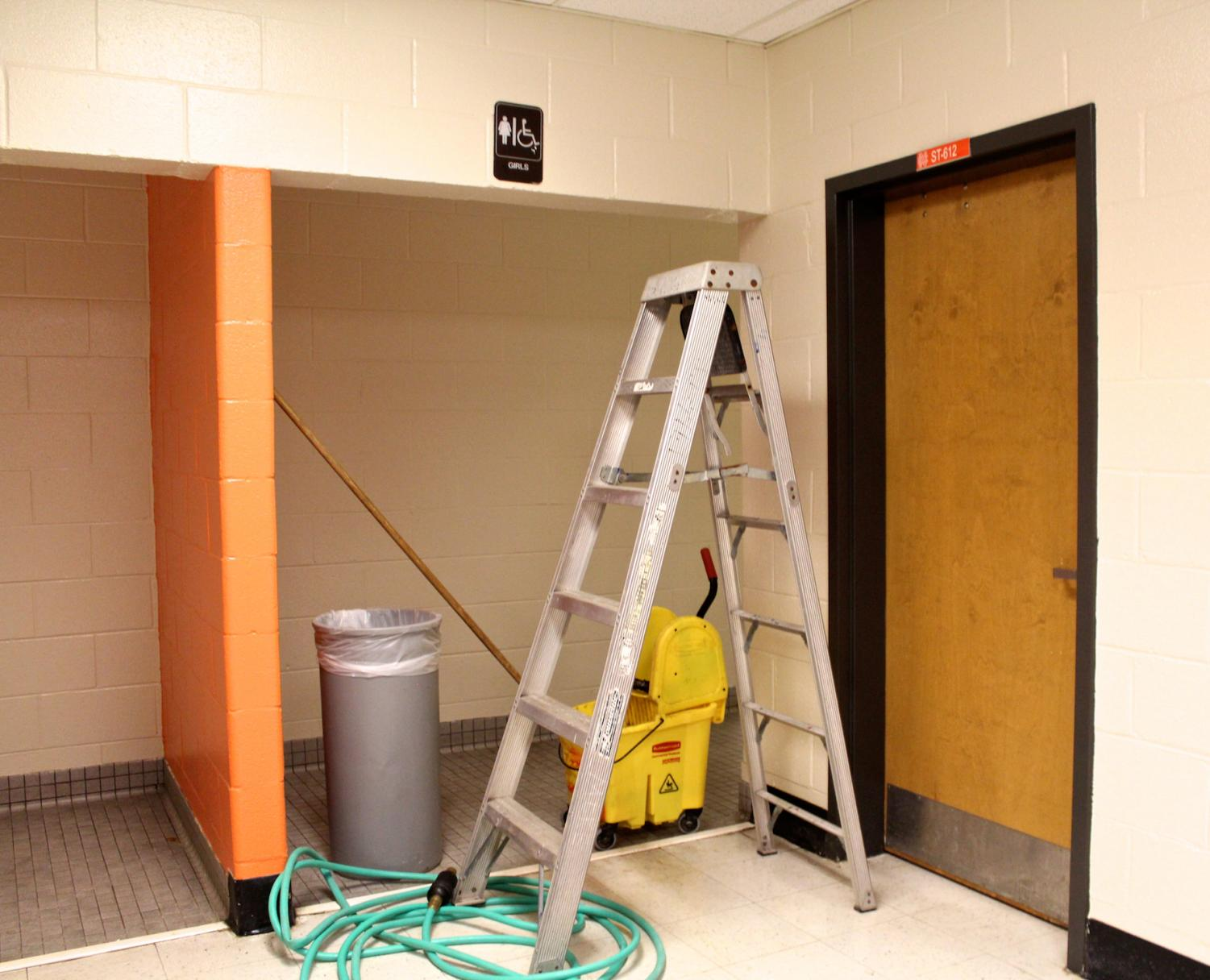The custodians created a barricade outside of the girls' bathroom in the 600 hallway using a ladder, trash can, hose, mop, and bucket to stop people from coming inside. The restroom, currently closed for maintenance, will reopen shortly.