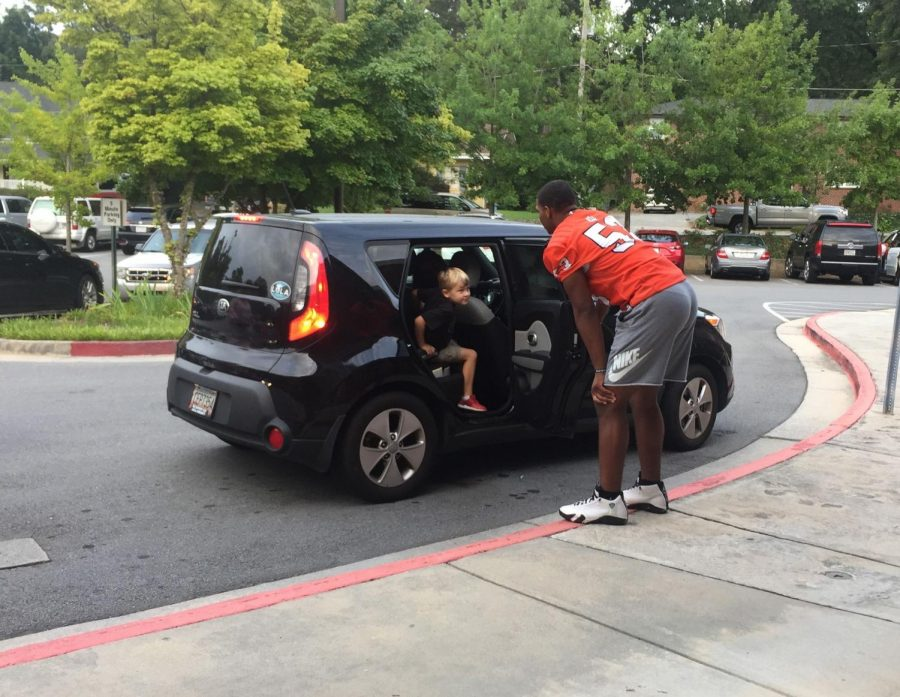 "Every home game, the football players wake up early to open car doors for the younglings at a variety of different elementary schools in the county. They bring spirit and excitement to teachers and students, impacting and touching their lives one car door at a time.  ""When I first saw them, I thought that it was a party,"" first-grader Elizabeth Holt said."