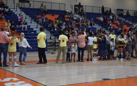 The senior volleyball players and their families line up shortly before the start of the game to address the crowd. The seniors honored include (in order of appearance) Taylor Hall, Jada Reed, Isabella Rodriguez, and Alison Weigel.