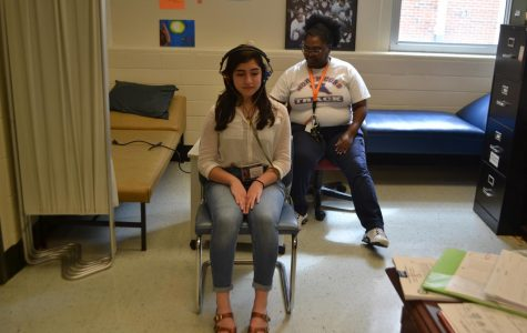 Sophomore Julyana Ayache sits with the nurse for her annual hearing and vision test. If the student does not pass the screening, they must visit  a hearing or vision specialist to make sure their eyes and ears function correctly.
