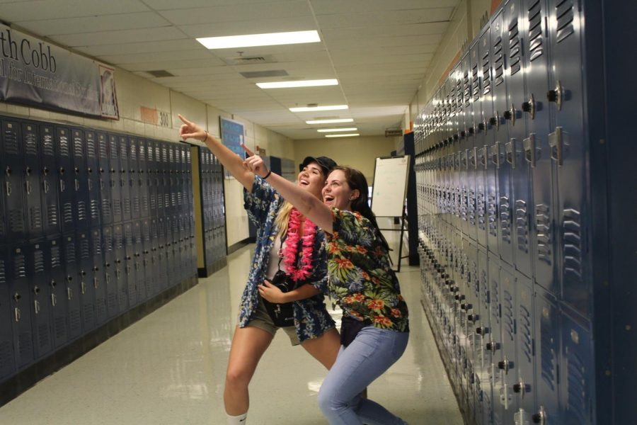 "NC's resident tacky tourists seniors Gina Nordman and Danielle Farmer began their sightseeing in the hallways of NC, flaunting their bulky cameras and hats that scream ""adventurer."" The Hawaiian shirts completed their looks and emulated the vacation vibes they strived for."