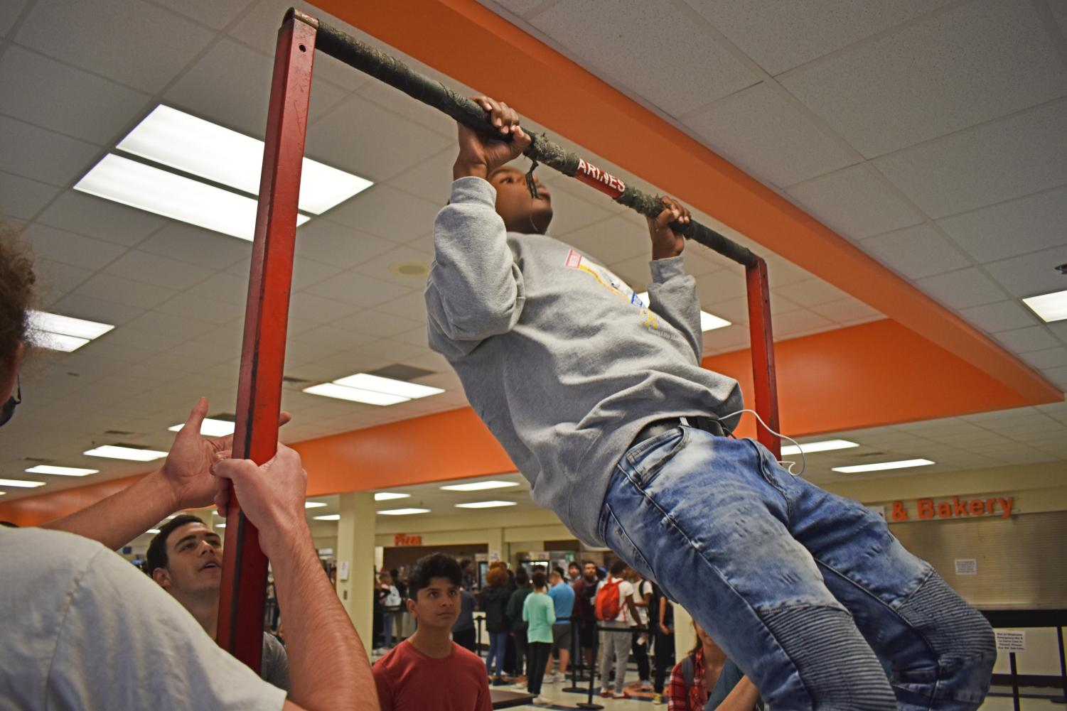 "The United States Marine Corps Recruiting Service set up a recruiting station today in the main cafeteria. Students lined up to take turns doing pull-ups, and whoever successfully completed 20 received a t-shirt. Senior Oscar Ngugi attempted, but could not complete the challenge. ""The first ten or so were easy, but I got really tired and I couldn't do any more,"" Ngugi said."