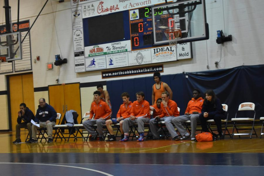 At Wednesday's match against the Harrison Hoyas, the Varsity Warriors Co-ed Wrestling team observes one of the bouts; like with all high school wrestling matches, a wrestler will face off with their opponent in three rounds, each lasting 3 minutes. This applies to all twenty-two members of the team.