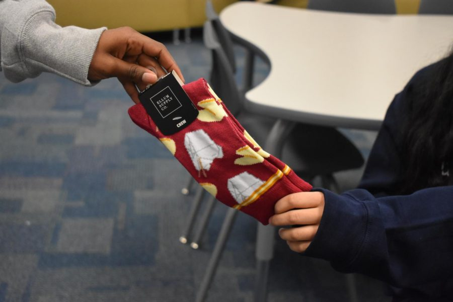 """The Magnet program will hold their first ever sock exchange event this year on December 18 during all lunches in the Magnet Lounge. The event allows Magnet students to meet other peers within NC through their shared admiration of socks. """"The sock exchange is a really cool opportunity for students to find creative, fun, and crazy socks. You bring it into your bundle teacher and they put it in a paper bag and you explain why you chose these crazy socks. The ultimate goal is for us to get to know each other a little better and create a community within the Magnet program and I am excited to be a part of it. I've already gotten several crazy pairs,"""" AP Lang teacher Lindsey Theaker said."""