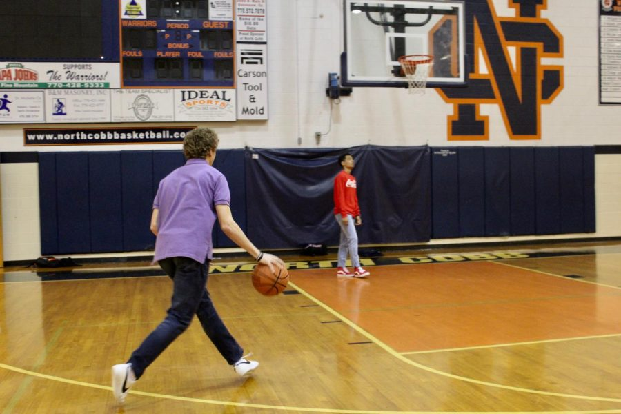 Sophomores Drew Dodd and Tyler Gorsuch warm up for the basketball season with a quick one-on-one practice. The boys threw free throw basketballs into the hoops of the gym and challenged each other's skills. The boys look forward to making the team and bringing home the gold for NC.