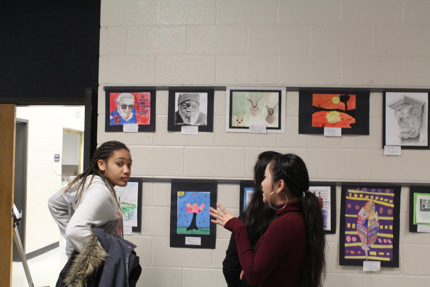 Visiting students from Awtrey Middle School admire the work from Mrs. Dowling's & Mrs. Brewer's art class. Yesterday marked the beginning of the NC Visual Art class' annual Art Show; during this exhibition, up and coming art students from all of the NC feeder schools (Barber, Paulding, etc.) come to analyze the art of Brewer's and Dowling's class, so as to gain a better understanding of techniques used.