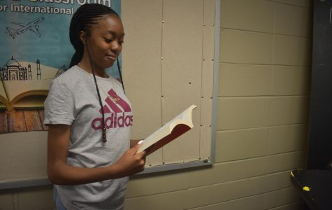 Magnet junior, Precious Ajero stands reading a book to learn about college and the college application process. Ajero takes science and math class to prepare her for her future. She plans to follow in a career as a pediatrician and study at Emory University.
