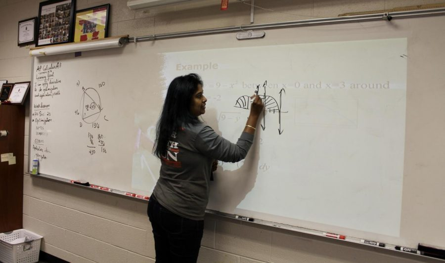 """AP Calculus teacher Deepa Stephen teaches the applications of integral calculus to her class. Stephen, with experience teaching in India, the United Kingdom, and the United States, decided to live in the US and teach for several years. """"People are always saying things about the US education and all that, but they very often forget the freedom here. Here its a lot about your identity, and not about what your parents are doing or what opportunities are only available in your country. It's a great thing to live here,"""" Stephen said."""