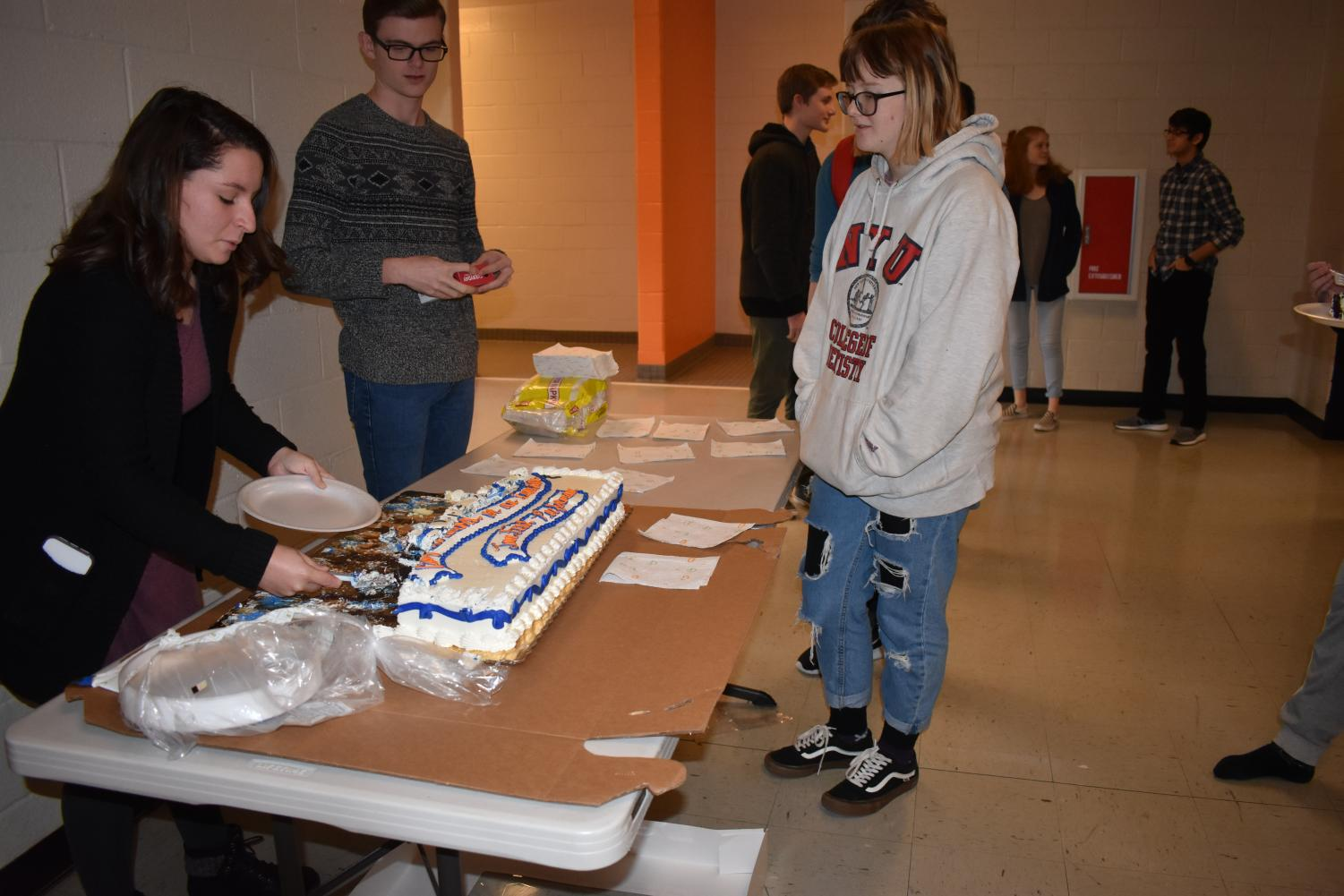"""Kennesaw State student teacher, Brianna Curtis and Senior Andrew Riner distributed cake to students to celebrate the band's performance at the University of Georgia. Students enjoy the celebratory cake from their success at their trip on Friday, January 18. """"We performed at UGA because we submitted a recording and they accepted us. It was fun because we got to perform in front of all these students from around Georgia,"""" senior Sarah Goddard said."""