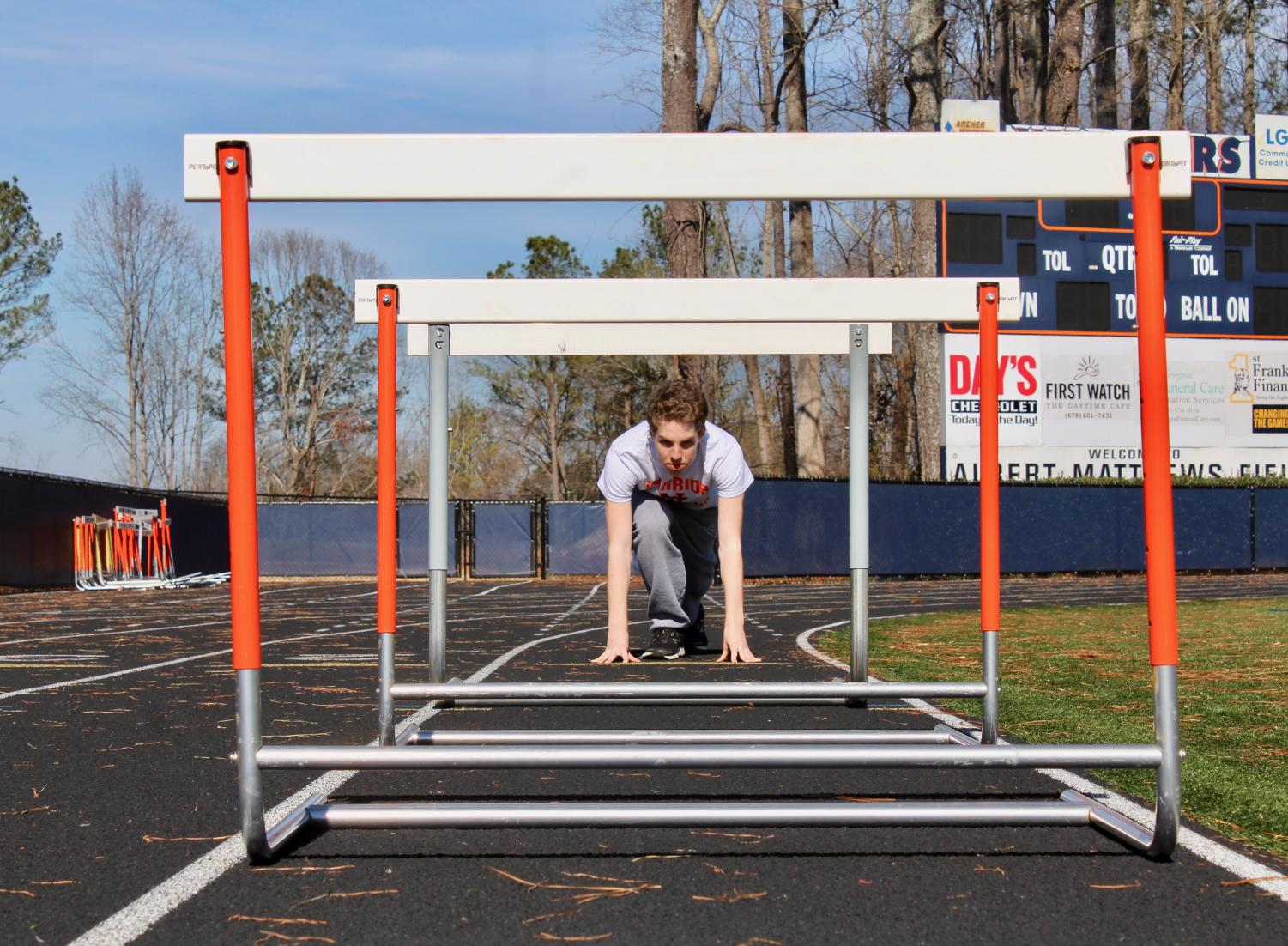 """Magnet junior Isaac Stobo prepares to jump over this season with success. After three years  of NC track, Stobo hopes to make it to state and improve his time in the long distance events he runs. """"This year my main goal is to make it to state and to accomplish this I am not going to get sick since I missed half of the season last year,"""" Stobo said."""