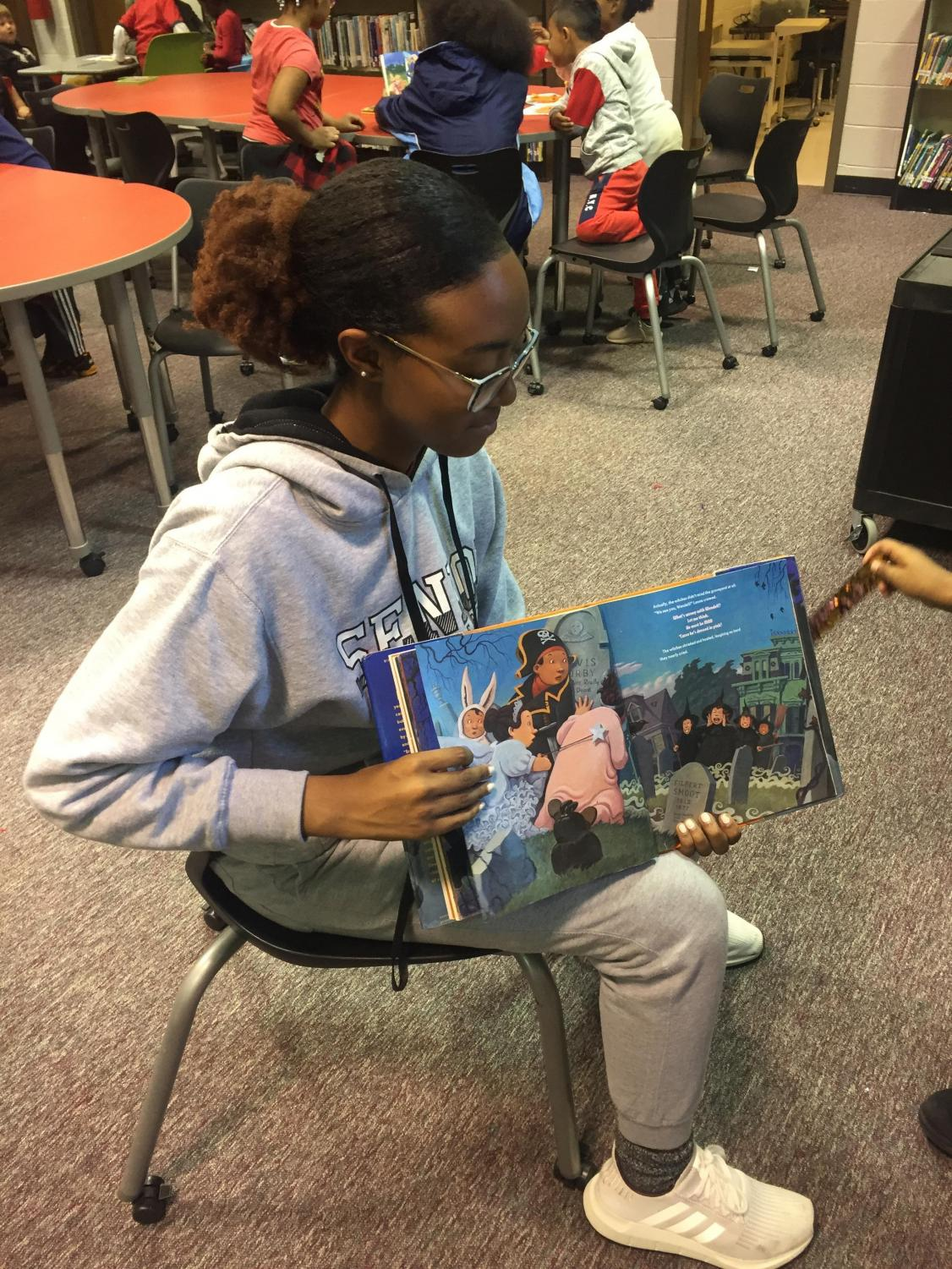 """Senior and club president Madeline Toombs reads a book to the children at Baker Elementary School. She hopes to grow the club and encourages other students to attend and meet these children. """"I love socializing with all of the different personalities of the kids and experiencing a completely different generation,"""" Toombs said."""