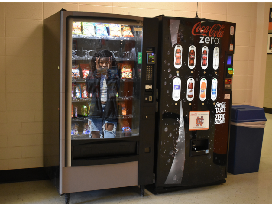 """As an avid foodie, senior Neffy Shabazz loves to use the vending machines on campus daily. However, Shabazz's love for vending machine rations took a turn for the worse as the vending machine sucked her in through the cash inserter. """"I don't know what happened; one second I was standing outside the machine, the next I was inside freaking out,"""" Shabazz said. Janitors work tirelessly to break Shabazz out and estimate she will return to the halls of NC on April 1."""