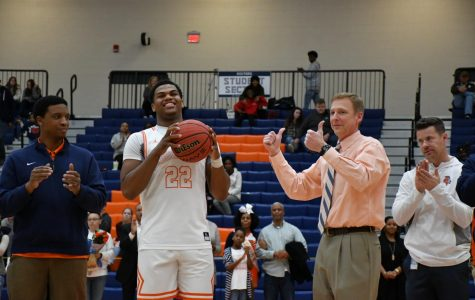 """Varsity Boys Basketball coach Terry Gorsuch accompanies senior player Kevin Hester during senior night, saying a farewell to a significant part of his 2018-2019 season coaching basketball. """"Each Senior group is special—these four seniors have been awesome and I will truly miss them. Shota Suzuki, Kevin Hester, Josh Moten, and Tyrese Crawford have done so much for the program the last four years,"""" Gorsuch said."""