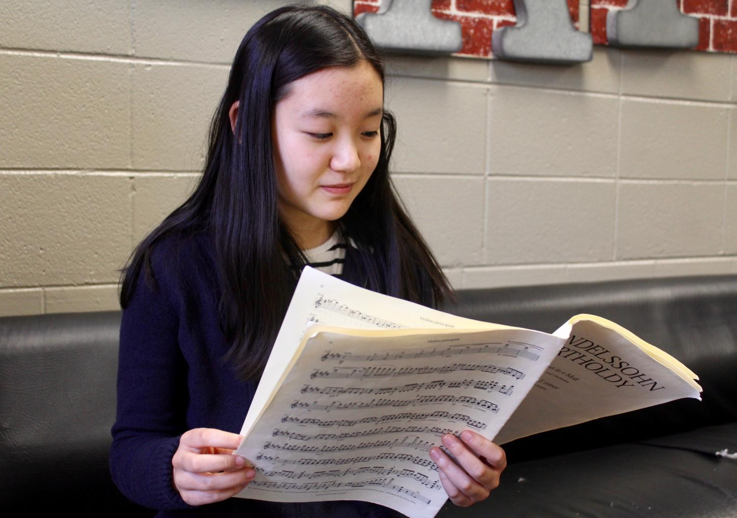 "Sophomore Hannah Lee studies sheet music for an upcoming performance. A talented violinist, Lee plays in both NC's chamber orchestra and the Georgia Youth Symphony Orchestra (GYSO). ""Don't give up, even though you feel like it's really hard. Just keep practicing, and your hard work will pay off,"" Lee said."