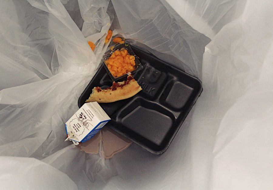 A fresh pizza crust, container of juicy mandarin oranges, and a half full carton of chocolate milk—all perfectly edible—sit at the bottom of the trash can at the beginning of B lunch. What's with all the waste?