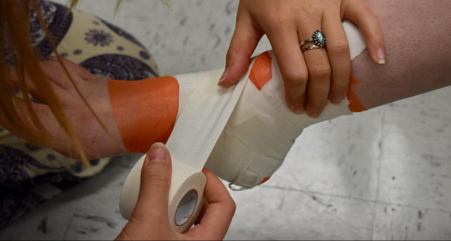 Nati Duron captures the wrapping of an ankle to stabilize certain joints within the ankle. This wrap helps many basketball players in the recovery process in an ankle sprain, the partial or fully tearing of a ligament within the ankle.