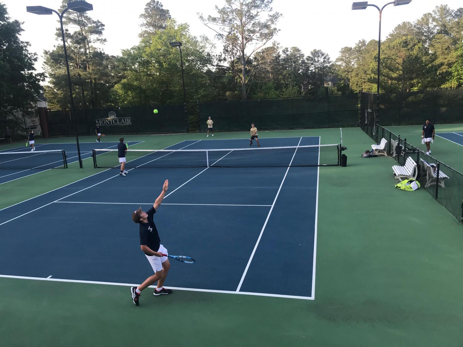 "Despite the heckling from Brookwood students, which NC athletic director Matt Williams immediately addressed, senior Reed Walker (serving) and freshman Payton Stack (net) fought through a hard match against their opponents, representing their fellow teammates and school. ""Watching my teammates play always motivates them. Reed and Payton are amazing players and I'm so happy to have them competing with me. I'm going to miss Reed and all of the other seniors, but I'm confident that Payton and I will maintain the NC tennis legacy,"" freshman varsity player Lorenzo Alarcon said."