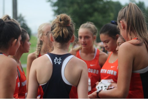 "Varsity Girls circle up before their race creating a huddle that as much unites them one to the other as it may unnerve their opponents. ""I like the community that we share and how everyone supports each other in Cross Country,"" senior Reagan Beach, leader of the ""Hype Circle,"" said."
