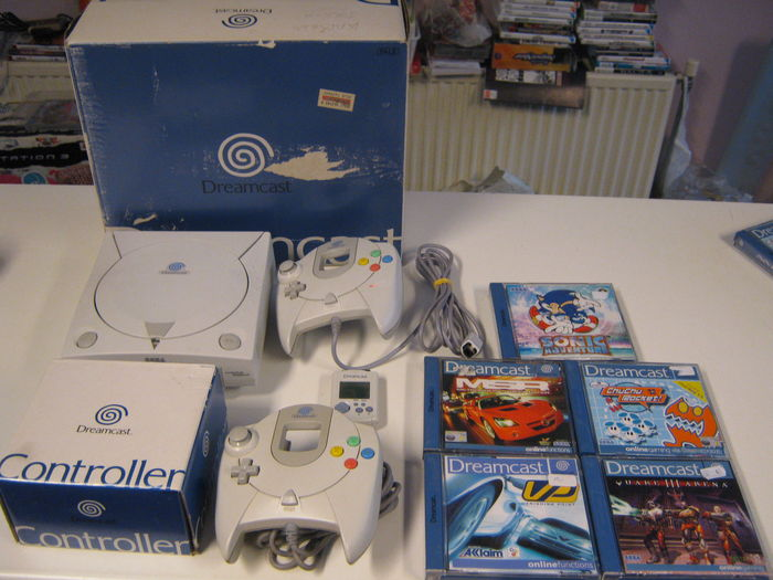A+vintage+Dreamcast+box+set+%28containing+from+left+to+right%2C+clockwise%3A+Sega+Dreamcast+system%2C+controller%2C+copies+of+Sonic+Adventure%2C+Chu-Chu+Rocket%2C+Quake+3+Arena%2C+Vanishing+Point%2C+and+Metropolis+Street+Racer%2C+and+a+second+controller%29+lays+on+a+table.+Released+on+September+9%2C+1999%2C+in+North+America%2C+the+console+marked+the+end+of+Sega%E2%80%99s+tenure+as+a+console+maker.+Though+a+failure+in+its+time%2C+due+in+large+part+to+the+company%E2%80%99s+prior+failures+and+stiff+competition+from+the+Playstation+2%2C+the+console+now+holds+a+reputation+as+the+most+influential+consoles+of+all+time.
