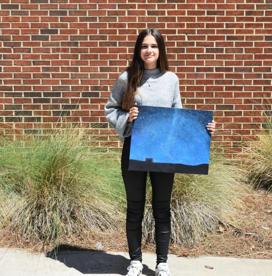 International exchange student, Aixa Rúa Rodríguez, stands on her temporary school campus sharing one of her paintings from her AP Drawing and Painting class.  The painting features a star-filled night sky presumably from her hometown of Boadilla, Spain. As a sibling of a former exchange student, Rodriguez came with a good understanding of life in America.