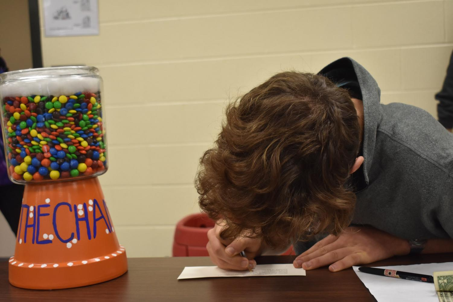 Senior Chandler Quaile eagerly fills out a sheet of paper in the freshman academy, hoping to end up the lucky winner. Sponsored by the Chant and promoted here by senior staffers Haley Kish and Nia-Simone Sherwood (not pictured), this event sees students attempt to guess the number of M&M's within the jar pictured above: those who guess correctly will win a wristband ticket for the upcoming Music Midtown. The competition starts Monday, September 9, and ends this Wednesday, September 11.