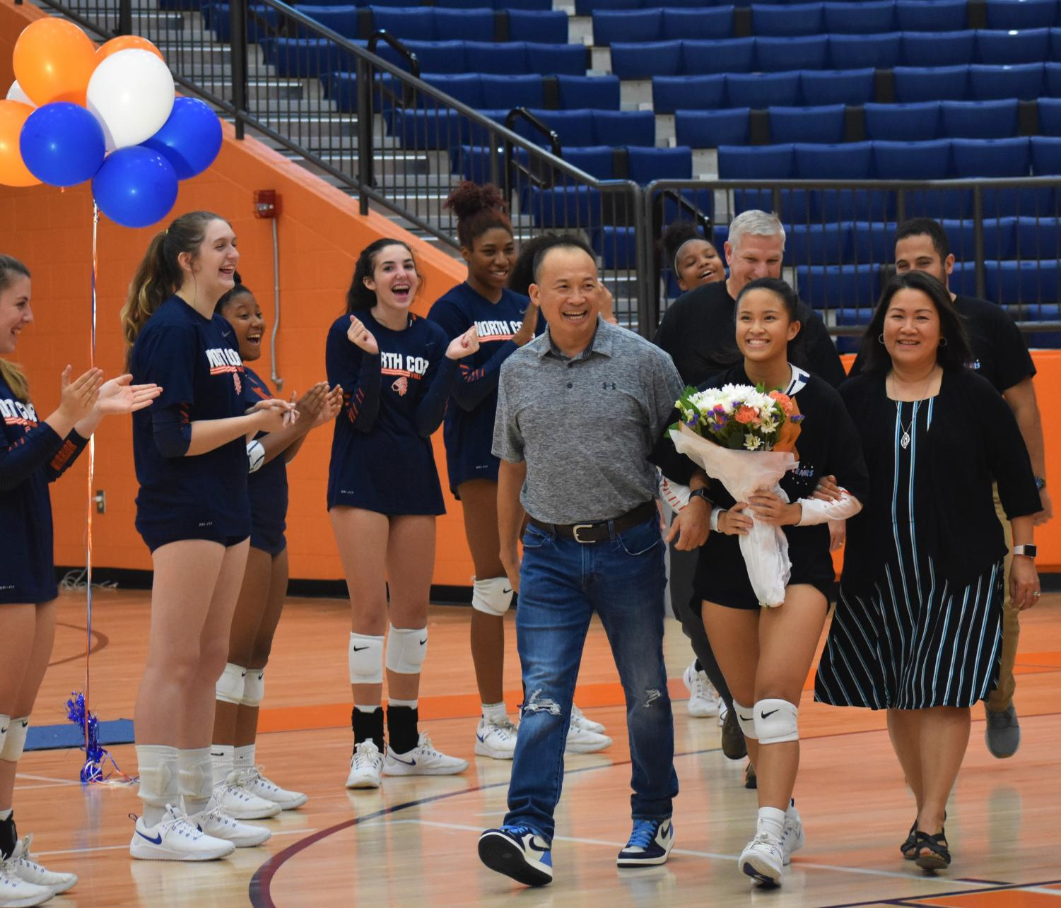 """Escorted by her parents and older brother, Tran received overwhelming recognition for her four years playing as a varsity volleyball player on Thursday night. The stands, full of Tran's best friends enthusiastically cheered on their friend as they listened to her favorite high school memories and her aspirations for the future. Tran's team will dearly miss one of their favorite teammates when Tran graduates this spring. """"Nicole is our best passer on the team, and she is leaving behind a huge legacy to the NC volleyball program,"""" said junior Ivanova"""