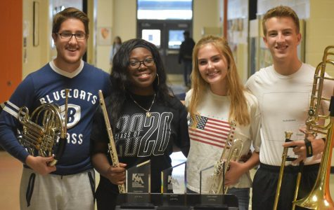 "Drum majors Reese McGee, Ola Otis, Lillian Southall and Jonas Ventresca stand behind their awards earned at Kennesaw Mountain Marching Invitational. The students earned awards including ""Fourth Place Overall"", ""First Place Class AAAAA"", and ""Outstanding Drum Major""."
