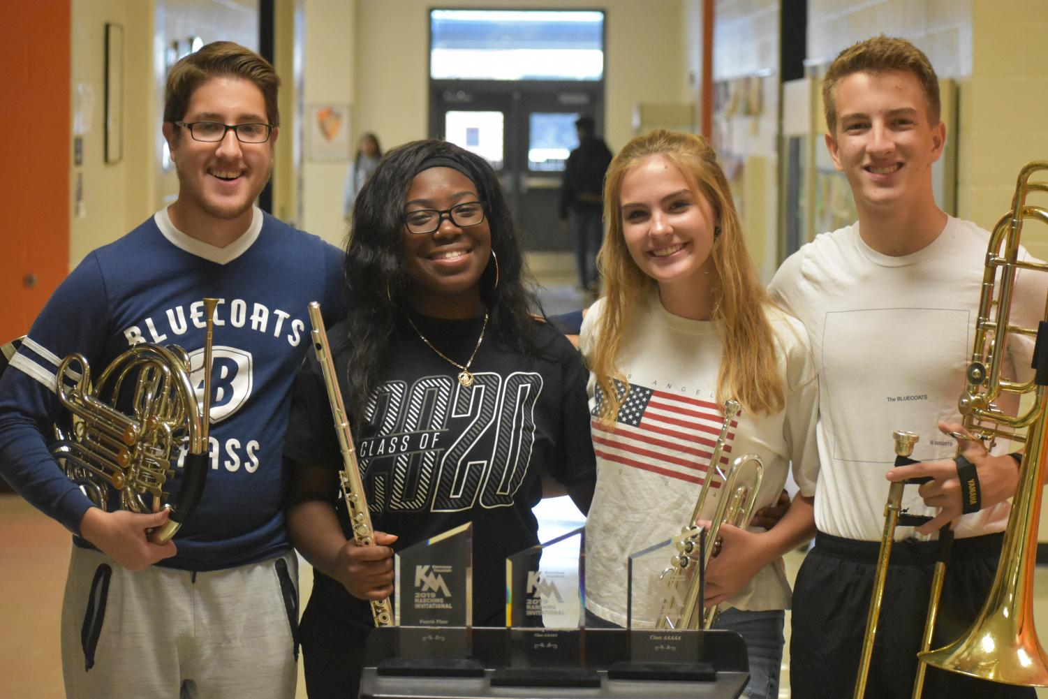 """Drum majors Reese McGee, Ola Otis, Lillian Southall and Jonas Ventresca stand behind their awards earned at Kennesaw Mountain Marching Invitational. The students earned awards including """"Fourth Place Overall"""", """"First Place Class AAAAA"""", and """"Outstanding Drum Major""""."""