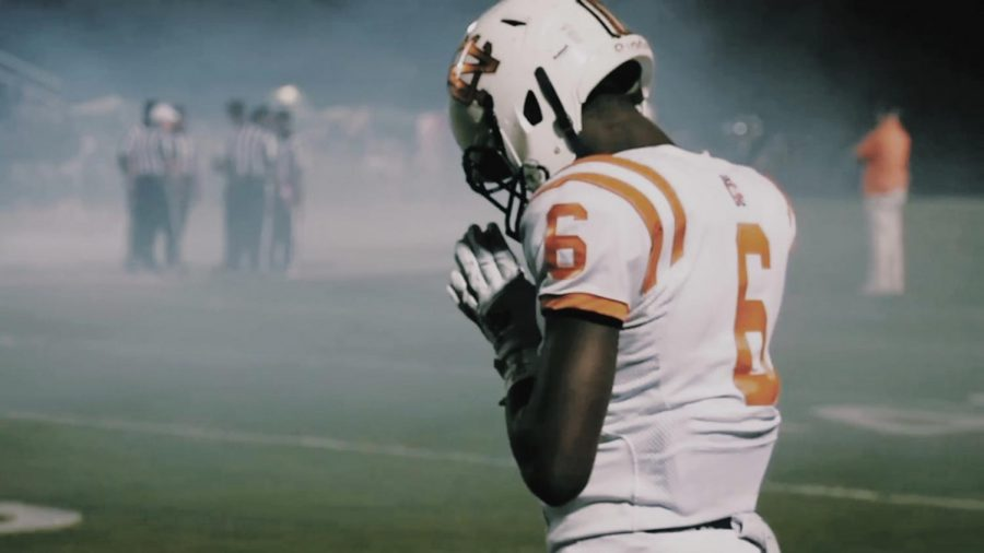 NC sophomore wide receiver Sam Mbake practices his traditional pre-game rituals, while the smoke clears from Cobb EMC Mustang stadium. Mbake finished the night with a receiving touchdown and multiple catches that fueled the Warrior's fire. Junior quarterback Trevor Lovett and Mbake seem to connect game in and game out, working together to make multiple touchdowns this season.