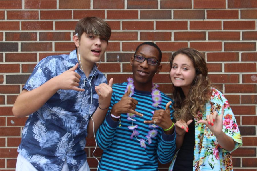 """Surfs up at NC as students rode the PSAT wave on Wednesday. Amber Roldan,  Ashu Ebot-Tabi and Peyton Stack take time for an iconic brick wall picture to show off their Hawaiian leis. Their fingers show the traditional symbol for """"surfs up"""" that surfers repeat to keep high spirits among their peers."""