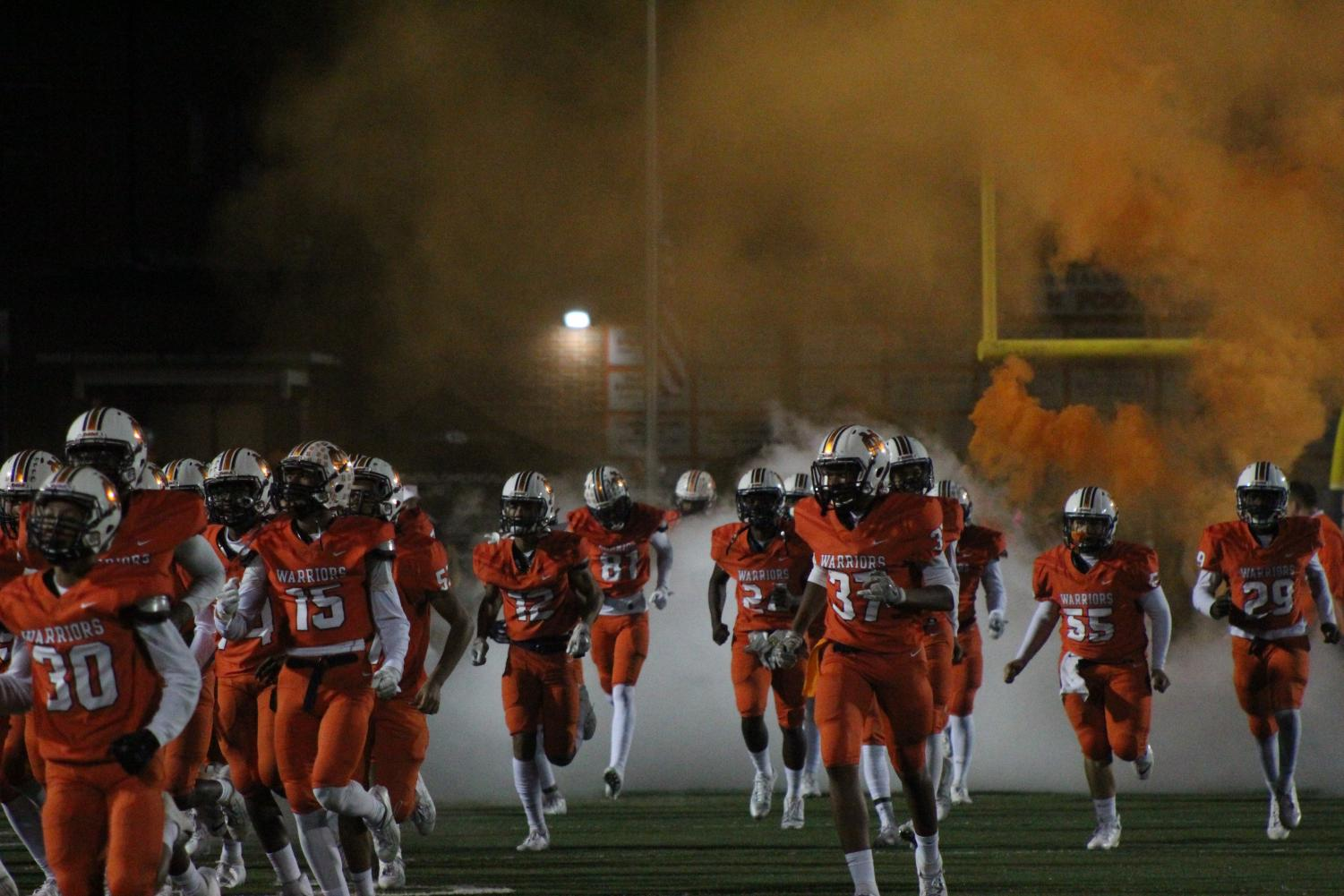 The NC varsity football team runs through the NC banner making the crowd excited. Orange and white smoke surround the players as they jump and cheer while preparing to beat North Paulding.