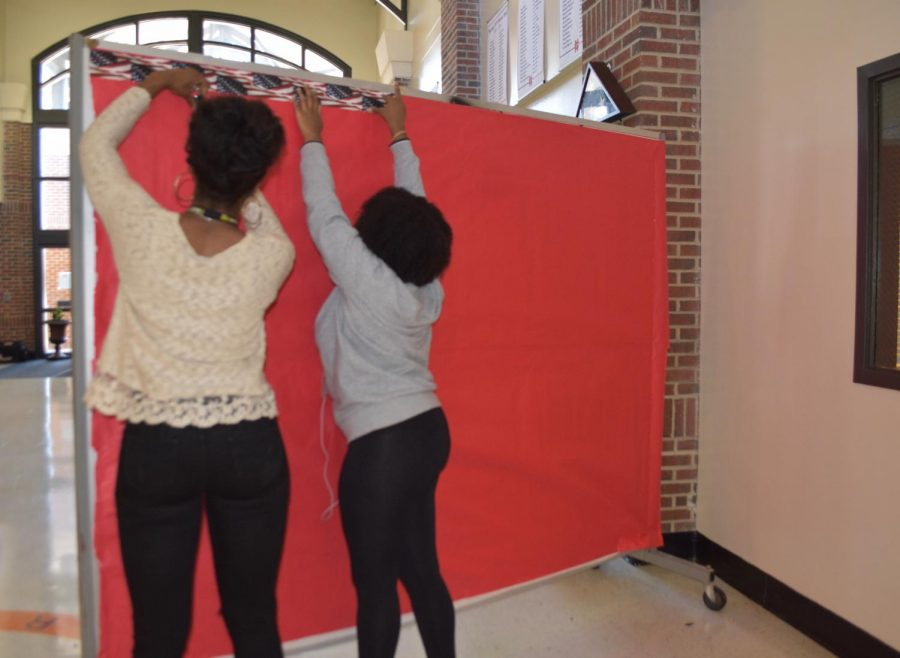 Students hang up decorations to celebrate Veterans Day on Monday, November 11. The display will stand in the main building, across from the attendance office. The bulletin board will include American flags, pictures of veterans and quotes.