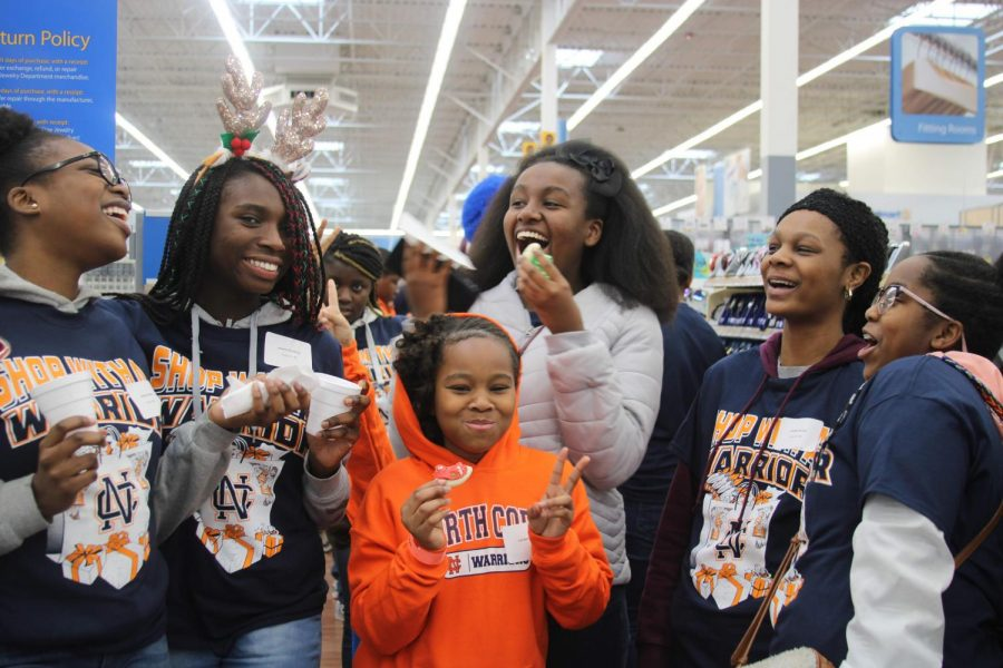 Shop with a Warrior group members and their Little Warrior enjoy the treats provided by Wal-Mart after a long day of shopping for their family and friends. Laughter and happiness fill the environment as students and young children alike enjoy each other's company, making new memories worth cherishing.